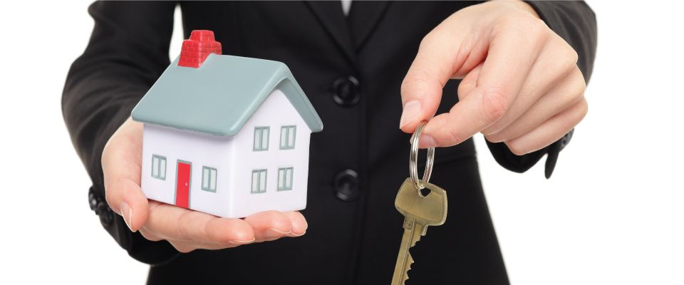 realtor holding key and house